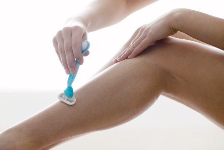 Woman Shaving Legs --- Image by © Rick Gomez/Corbis